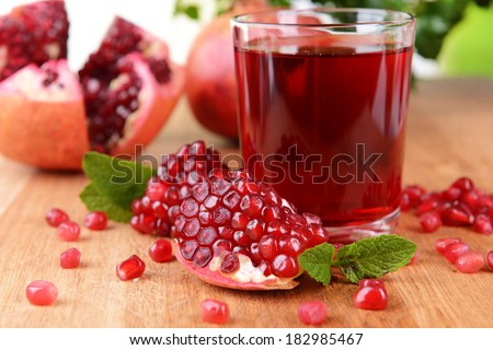Ripe pomegranates with juice on table close-up - stock photo