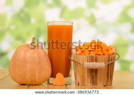 Ripe pumpkin bucket with dice and a glass of juice on the abstract green background. - stock photo