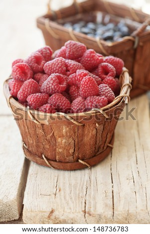 Ripe raspberries and blueberries in a basket - stock photo