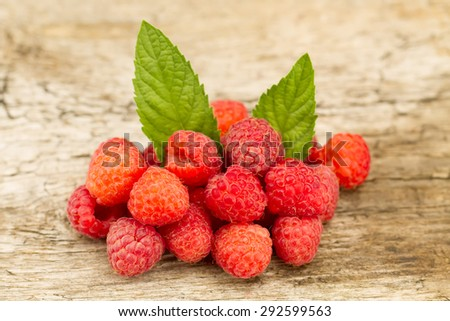 ripe raspberries with mint leaves closeup on wooden background, top view - stock photo