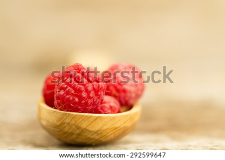 ripe raspberry in a spoon closeup on wooden background - stock photo