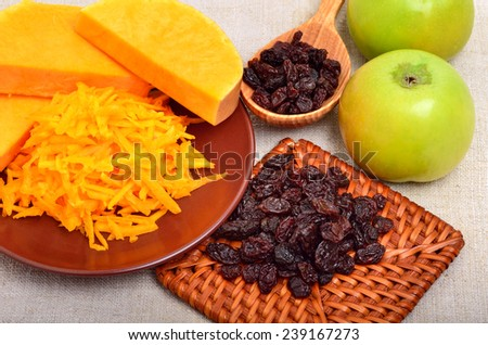 ripe raw pumpkin with grated pumpkin, apples and heap of raisins on the ceramic brown plate - stock photo