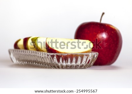 Ripe red apple and segments of apple on a plate - stock photo