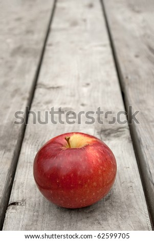 Ripe red apple on old wooden table, with copy space. - stock photo
