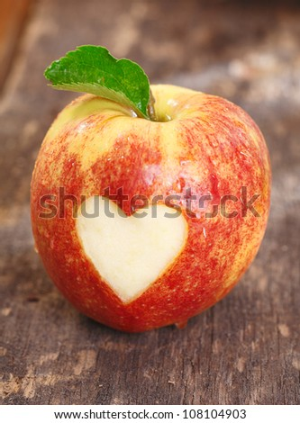 Ripe red apple with a heart shape neatly cut of the skin on a textured weathered wooden surface - stock photo