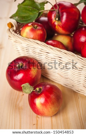 Ripe red apples in a basket on the table - stock photo