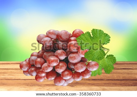 Ripe red grapes on wooden table over nature background - stock photo