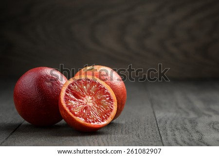 ripe red oranges on wooden table - stock photo