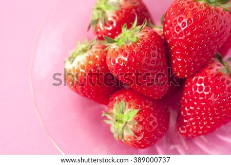 Ripe red strawberries on pink background - stock photo