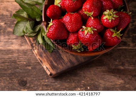 Ripe red strawberries on vintage wooden table - stock photo