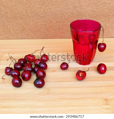 Ripe red Sweet Cherry and drink glass on a wood background. Selective focus (focus on foreground and center).Natural blur background - stock photo