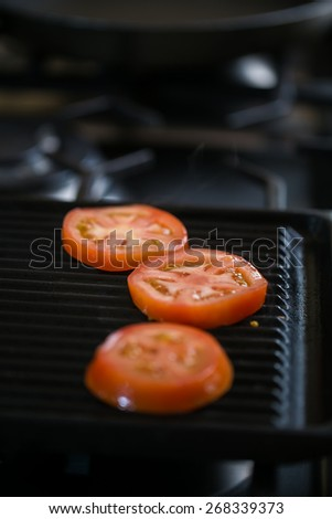 Ripe red tomato being grilled on a grill pan on a gas stove for breakfast - stock photo