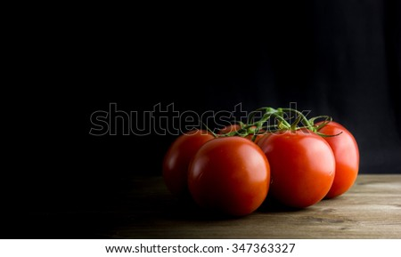 Ripe Red Tomatoes on a Wooden Table with Black Background. Dark Rustic Old Style - stock photo