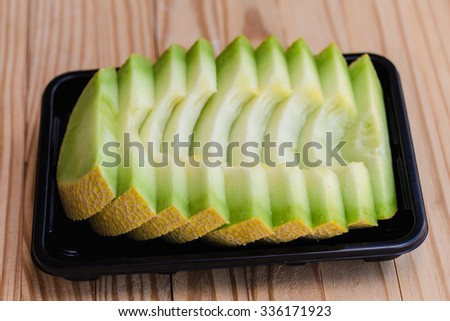 ripe slices of cantaloupe melon on wooden background  - stock photo