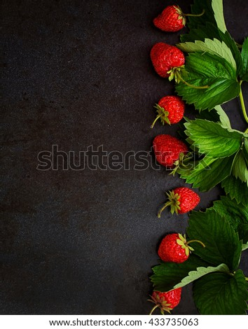 Ripe strawberries and leaves on a black background. Top view - stock photo