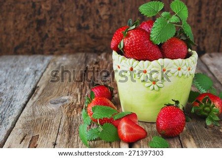ripe strawberries and mint leaves on a wooden background. berries from his garden.health and diet food. selective focus. copy space background - stock photo