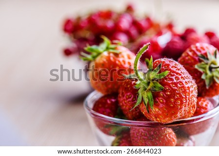 Ripe strawberries in glass plate on wooden table. - stock photo