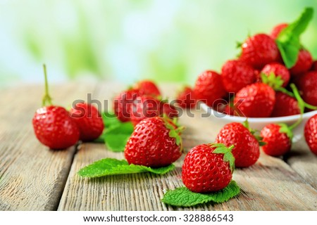 Ripe strawberries in saucer on wooden table on blurred background - stock photo
