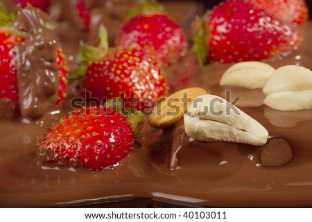 Ripe strawberry in dairy chocolate on a black background. - stock photo