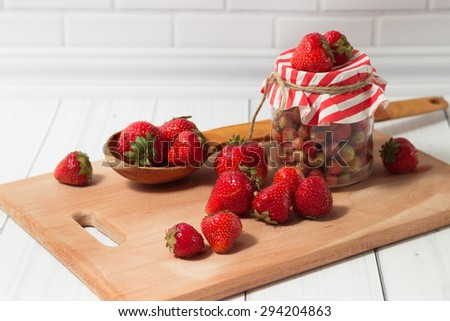 Ripe strawberry in the glass jar with striped top and wooden spoon on the board on the light grey background - stock photo