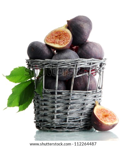 Ripe sweet figs with leaves in basket isolated on white - stock photo