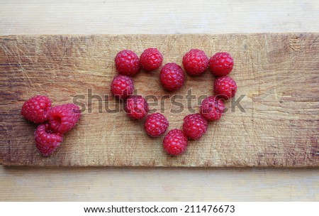 Ripe sweet raspberries arranged in heart shape on wooden cutting board. Closeup, daylight.  - stock photo