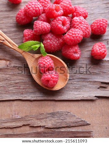 Ripe sweet raspberries in spoon on table close-up - stock photo