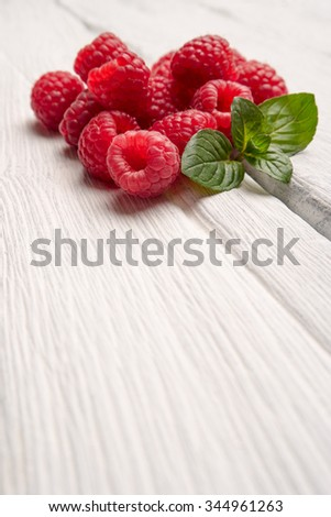 Ripe sweet raspberries on wood table background - stock photo