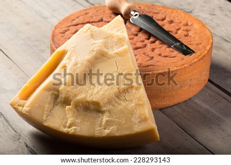 Ripe Swiss Sbrinz cheese on wooden table - stock photo