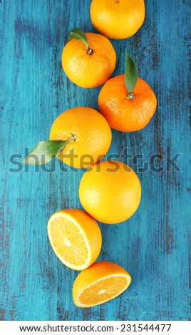 Ripe tangerines and oranges with leaves on wooden background - stock photo