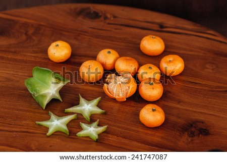 Ripe tangerines and starfrut (carambola) on wooden background. Mandarin oranges on wooden table - stock photo