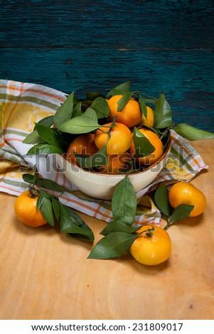 Ripe tangerines in a ceramic bowl - stock photo