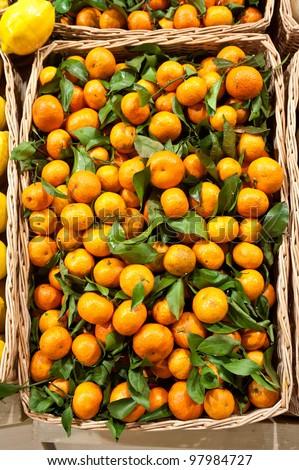 Ripe tangerines in a wattled basket - stock photo