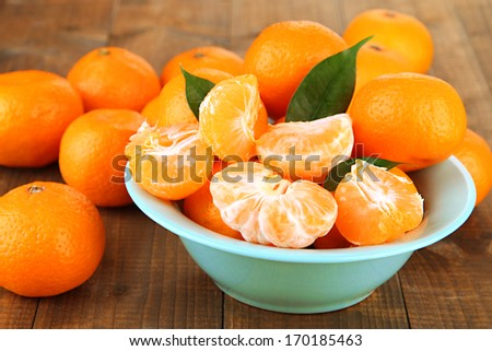 Ripe tangerines in bowl on wooden background - stock photo