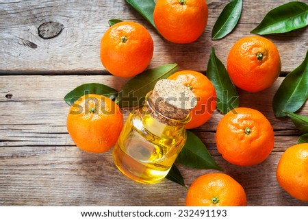 Ripe tangerines with leaves and bottle of essential citrus oil on a wooden table. - stock photo