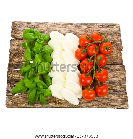 ripe tomatoes and mozzarella balls garnished with  basil  Italian food ingredients forming the italian flag on the old board isolated on white background - stock photo
