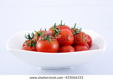 Ripe tomatoes in a white bowl - stock photo