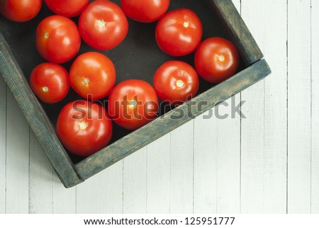 ripe tomatoes in rustic wooden box, on white wood table - stock photo
