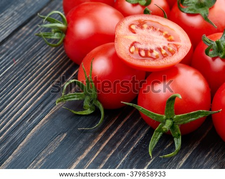 Ripe tomatoes on dark wooden background - stock photo