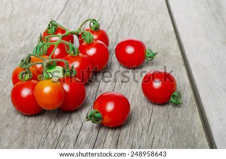 ripe tomatoes on rustic wood table - stock photo