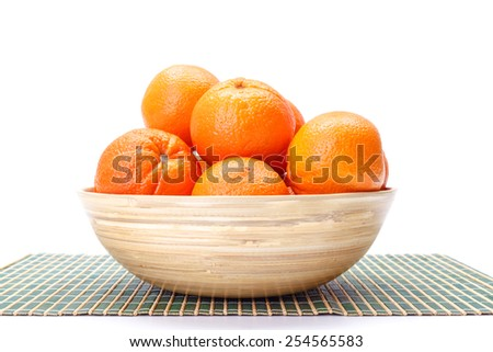 Ripe whole oranges in wooden bowl - stock photo