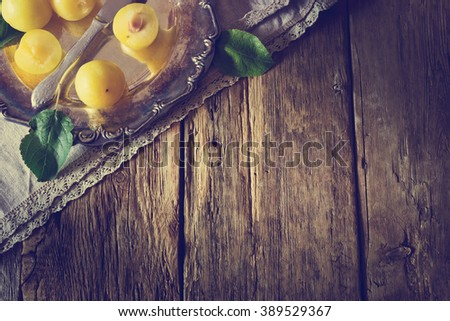 Ripe yellow plum in vintage metal plate on the table. View from above. Bio healthy food background. Organic fruits. Tinted image. Copy space background - stock photo