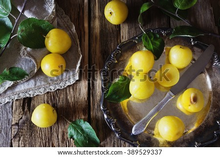 Ripe yellow plum in vintage metal plate on the table. View from above. Bio healthy food. Organic fruits - stock photo