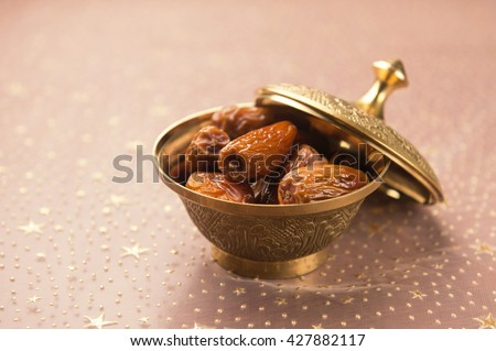 Ripened dates in a metal bowl. An important fruit in middle east. A golden bowl of dates. - stock photo