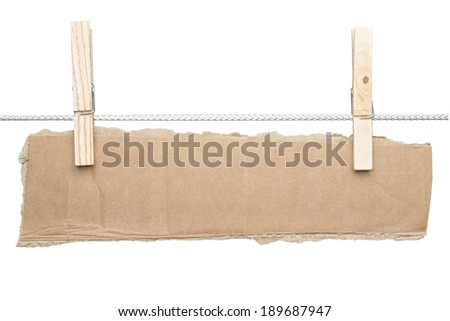 ripped piece of card board hanging on two clothespins, isolated on white. - stock photo