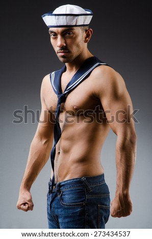 Ripped sailor against dark background - stock photo