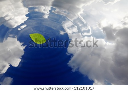 Ripple on the surface of water reflecting the blue cloudy sky with a single green leaf floating on it. - stock photo