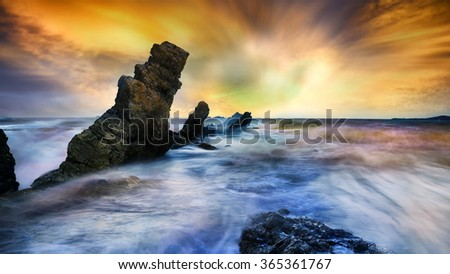 Ripple waves breaking on the rocks at the beach sunset light Focus on rocks foreground - stock photo