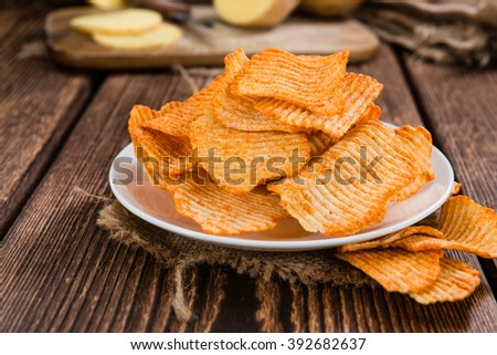 Rippled Potato Chips (selective focus) on an vintage wooden table - stock photo