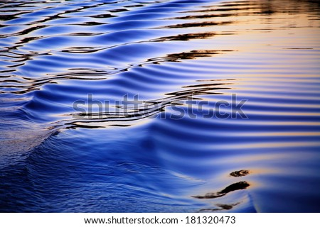 Ripples In The Wake Of A Pontoon Boat At Sunset On Whitewood Lake, Part Of The Huron River Chain Of Lakes, Southeastern Michigan, USA - stock photo